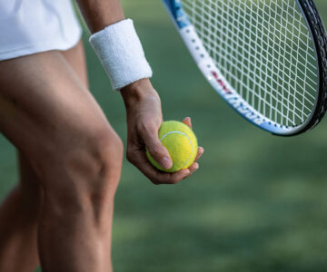 Close-up of racket and hand holding tennis ball