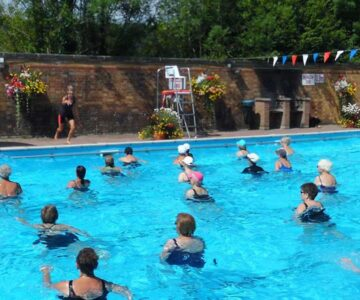 Aqua Workout class with teacher on poolside and participants in the pool on a sunny day