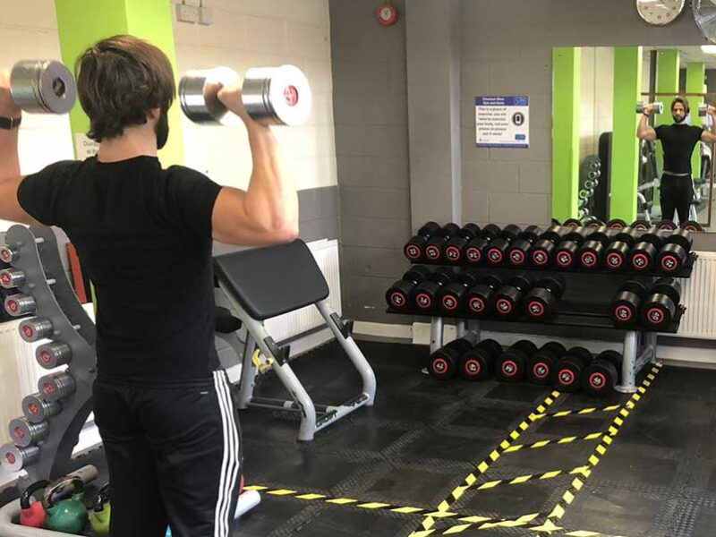 Young man in Chesham gym with weights, social distancing
